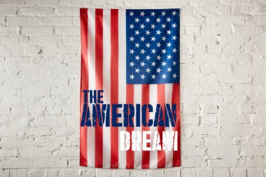close up view of united states of america flag with the american dream lettering on white brick wall