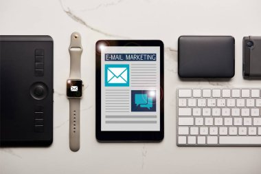 flat lay with various wireless devices and email marketing illustration on white marble surface