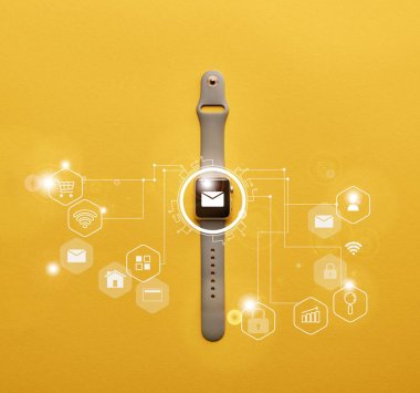 top view of smartwatch with system notification on yellow surface