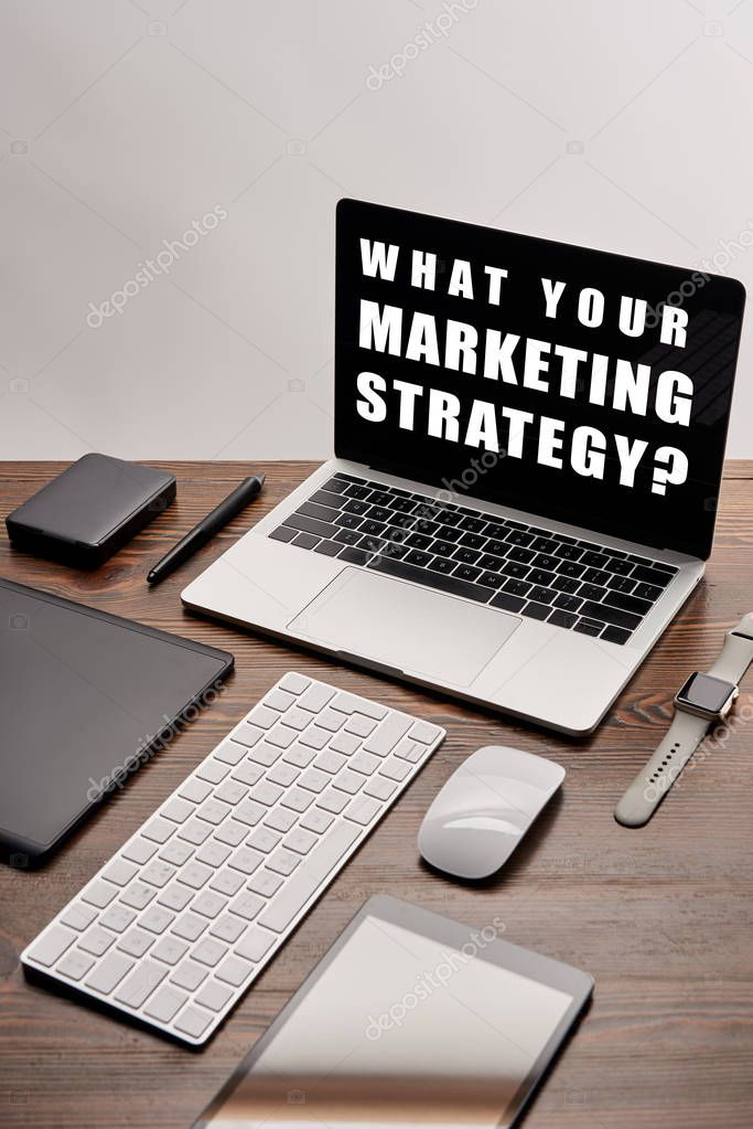 Flat lay of gadgets and laptop with what your marketing strategy question on screen at workplace isolated on grey