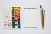 felülnézet album akvarell festékek és ecsetek, fehér háttér