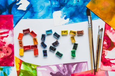 top view of paintbrushes, watercolor abstract drawings and art lettering made of paints