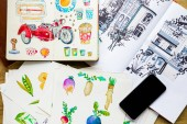 Photo top view of watercolor drawings and smartphone