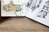 top view of drawings in albums on wooden background