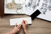 top view of womans hands drawing on paper, albums with paints and smartphone on wooden background