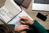 Rückenansicht eines Mannes, der ein Album auf einem Holztisch neben Laptop und Smartphone zeichnet