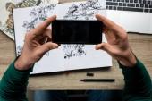 Fotografie částečný pohled člověka při kreslení foto na smartphone z alba leží na dřevěný stůl