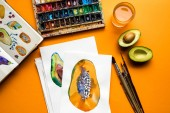 top view of colored paints, paintbrushes, sketchbook, drawings with avocado and papaya on yellow background