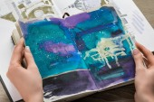 top view of female hands holding notebook with abstract blue drawing
