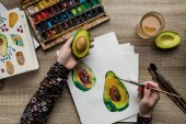 top view of female hands drawing avocado with watercolor paints and paintbrush on wooden table