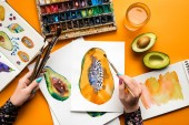 top view of female hands drawing avocado and papaya with watercolor paints, paintbrush on yellow table