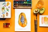pohled shora papája kreseb vedle barevné barvy a štětce na žlutém podkladu