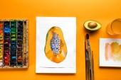pohled shora alba s papájou kreslení na žlutém pozadí vedle barevné barvy a štětce