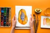 pohled shora na ženské ruce držící papája obrázek nad žlutá tabulka s nakreslenými nádobí