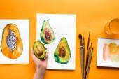 pohled shora na ženské ruky držící avokádo nad žlutá tabulka s výkresy ovoce a štětce