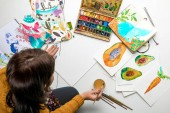 top view of woman preparing to paint with watercolors paints while surrounded by color drawings and drawing utensils