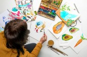 top view of woman painting with watercolors paints while surrounded by color drawings and drawing utensils
