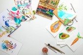 top view of multicolored watercolor paintings and drawing utensils