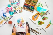 Fotografie top view of woman holding watercolor drawing while surrounded by color pictures