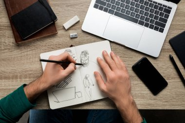 top view of mans hands drawing on album and smartphone next to laptop on wooden table