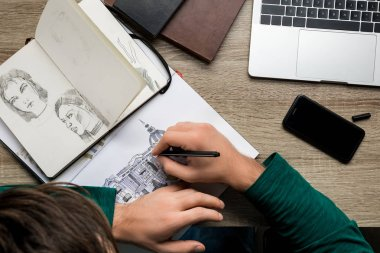 overhead back view of man drawing in album on wooden table next to laptop and smartphone