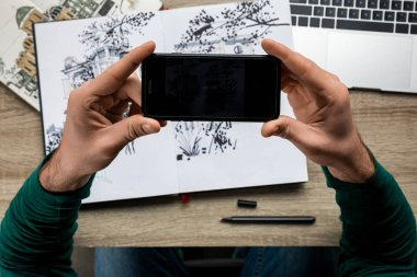 partial view of man taking drawing photo on smartphone from album lying on wooden table