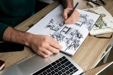 selective focus of mans hands drawing in album on wooden table next to  utensils