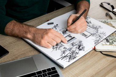 selective focus of mans hands drawing in album on wooden table next to laptop