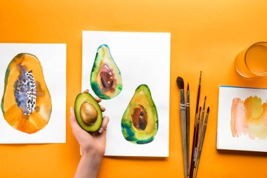 top view of female hand holding avocado over yellow table with drawings of fruits and paintbrushes