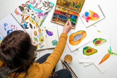 top view of woman women mixing watercolor paints while surrounded by color drawings