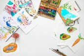 top view of colorful watercolor paintings and drawing utensils