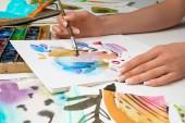 Selektivní fokus ženských rukou kreslení v albu s akvarel barvy a štětec