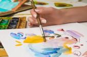 Selektivní fokus ženské ruky kresby na papíře s akvarel barvy a štětec