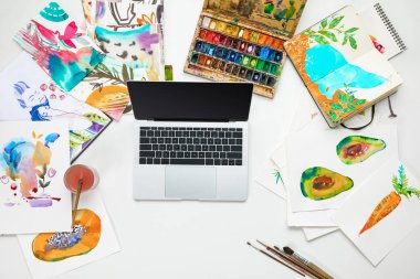 Top view of laptop surrounded by watercolors paints drawings stock vector