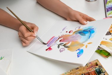 Selective focus of female hands painting with watercolors paints and paintbrush on white paper stock vector