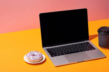 laptop with blank screen near donut and paper coffee cup on yellow surface and pink background