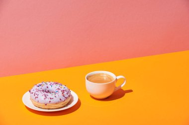 tasty donut with saucer and coffee cup on yellow surface and pink background
