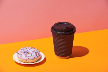 tasty donut with saucer and paper coffee cup on yellow surface and pink background