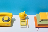 Fotografie multicolored notebooks, calculator, telephone and piggy bank on white desk and blue background
