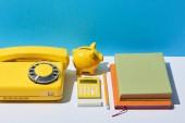 tarka jegyzetfüzet, számológép, telefon, malacka bank, fehér íróasztal és a kék háttér