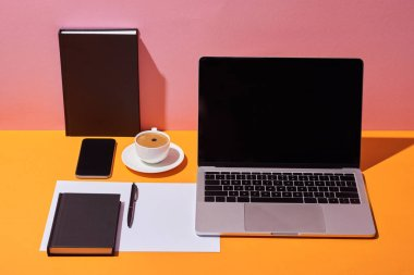 laptop with blank screen near coffee cup, saucer, pen, paper sheet and notebooks on yellow desk and pink background