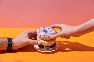 cropped view of woman and man taking tasty donuts on saucer on yellow desk and pink background