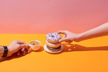 cropped view of woman and man taking tasty donuts on saucer and coffee cup on yellow desk and pink background