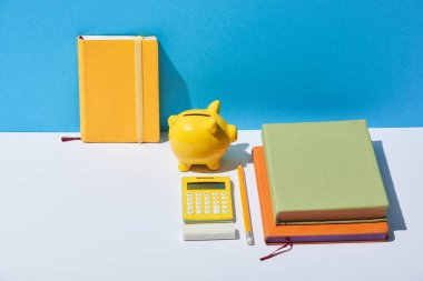 multicolored notebooks, calculator and piggy bank on white desk and blue background