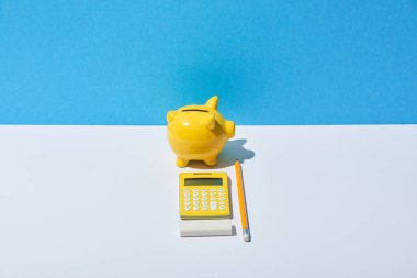 calculator, piggy bank, eraser and pencil on white desk and blue background