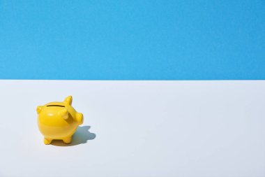 yellow piggy bank on white desk and blue background
