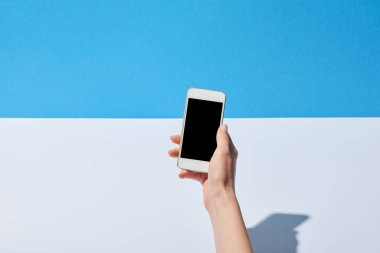 cropped view of woman using smartphone with blank screen on white desk and blue background