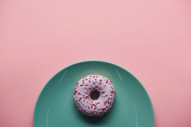 Top view of glazed donut on blue plate isolated on pink stock vector
