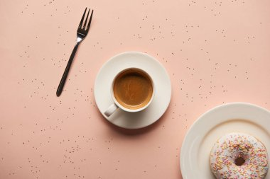 top view of sweet doughnut near cup of coffee and fork on pink background