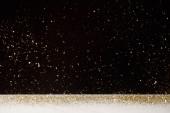 Selektivní fokus zlatých jisker padající na bílém stole izolované na černém